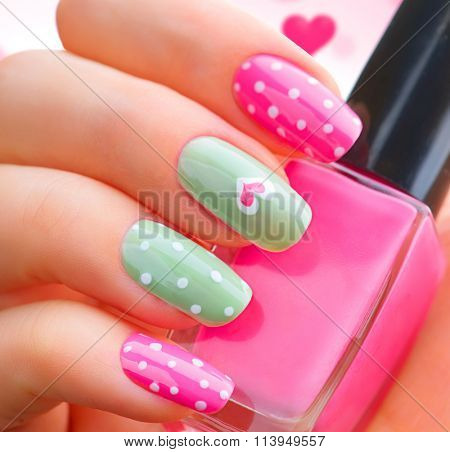 Valentine Nail art manicure. Valentine's Day Holiday style bright Manicure with painted hearts and polka dots. Bottle of Nail Polish. Beauty salon. Hand. Trendy Stylish Colorful Nails, Nailpolish