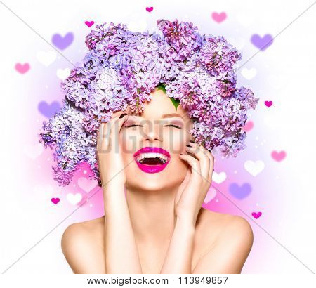 Beauty fashion model Girl with Lilac Flowers Hair Style. Beautiful Model woman with Blooming flowers on her head. Nature Hairstyle. Summer. Holiday Creative Makeup. Make up. Vogue Style