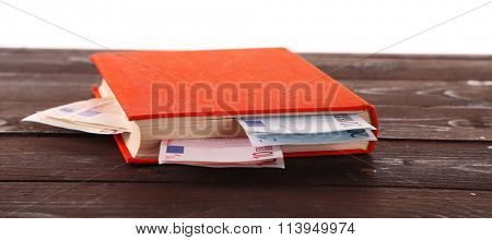 Red book with nested euro banknotes on white background. Stash of money