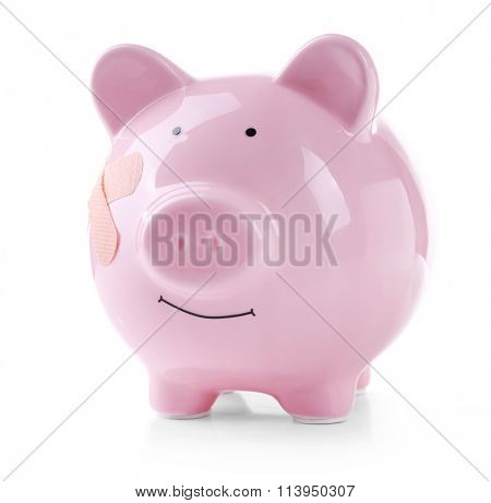 Piggy Bank with adhesive bandage, isolated on white