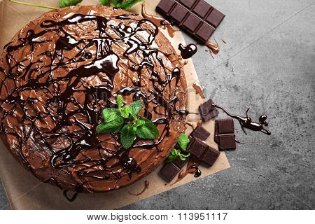 Decorated chocolate pie with mint and chocolate bar on grey table
