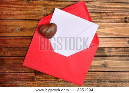 Red envelope with white paper and chocolate heart on table