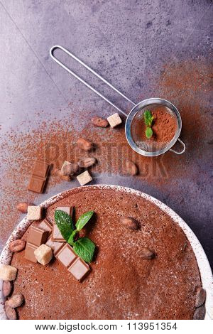 Chocolate pie with ingredients and sieve, closeup