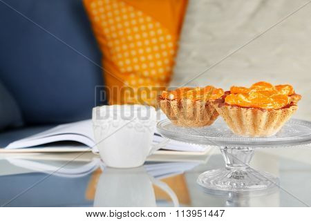 Sweet cakes with tangerines on table, close upbook