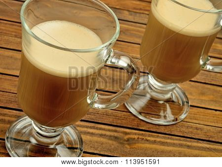 Two glasses with cappuccino on woden table