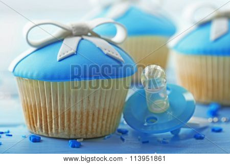 Tasty cupcake with bow and baby pacifier on color wooden background