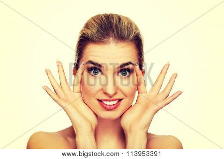 Young woman checking wrinkles on her forehead