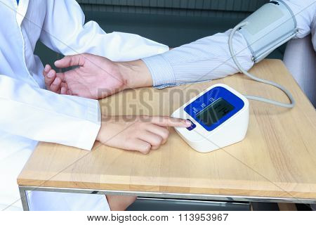 Woman Doctor Measuring Blood Pressure Of The Patient