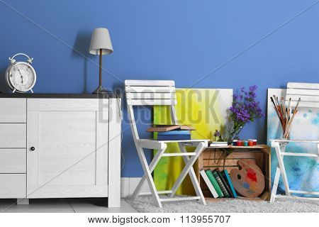 Room design with white furniture, bookcase, pictures, flowers over blue wall