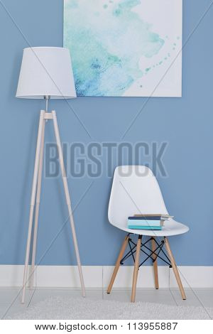 Room design with white floor lamp, chair and picture over blue wall