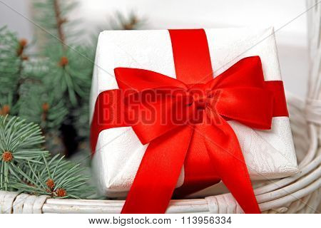 White gift box with red bow and spruce branches in wicker basket, close up