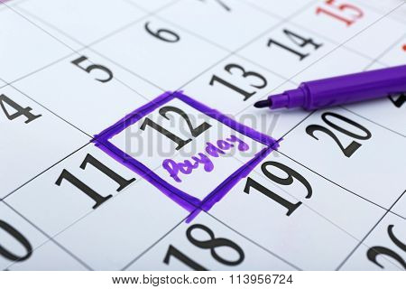 Payday concept. Calendar with purple felt pen background. Date in frame, close up