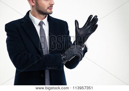 Handsome young man in black coat, white shirt and tie wearing leather gloves over white background