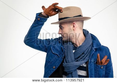 Profile of stylish attractive young man in hat and gloves isolated over white background
