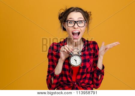 Amusing pretty young woman in plaid shirt and glasses holding alarm clock and shouting over yellow background