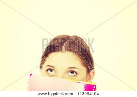 Teen woman hiding behind a notebook.
