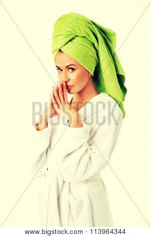 Woman in bathrobe clenching hands