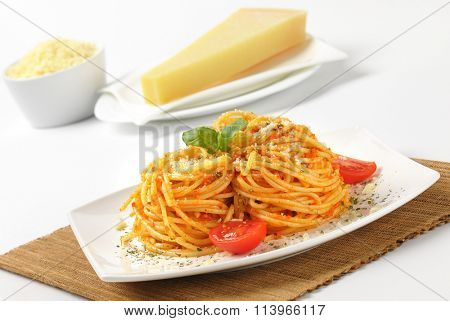 close up of cooked spaghetti with red pesto and grated parmesan cheese on white plate and brown place mat