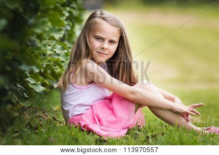Pretty little girl sitting in grass