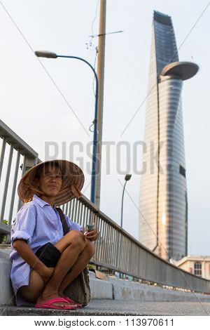 HO CHI MINH, VIETNAM - JAN 11, 2015: Local poor vietnamese man, in background Bitexco Financial Tower, 68 floors (and 3 underground) area 100,000 square metr, is the third tallest building in Vietnam.