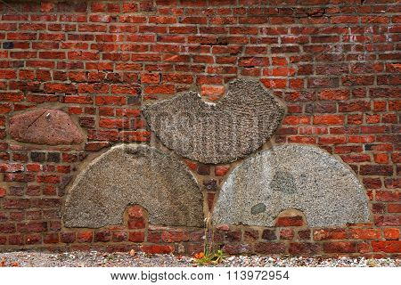 Architectural pattern of old and new bricks embedded in wall millstones. Restored brick wall in Koszalin, Poland.