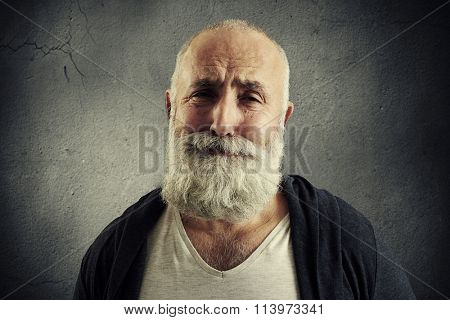 sorrowful senior man with grey-haired beard over dark background