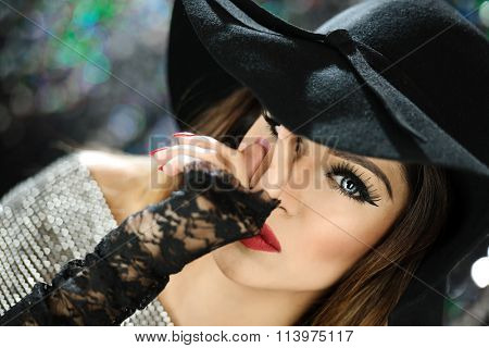 Beautiful female model in a hat with makeup and red lipstick