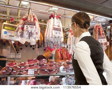 Woman buys smoked sausage in market. Woman looking to sausage in supermarket