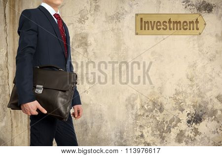 Portfolio investor. Businessman with briefcase on the background wall