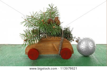 Wooden toy car with fir sprigs and bauble on a table over white background