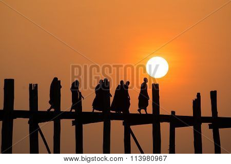 Silhouetted people on U Bein Bridge at sunset, Amarapura, Mandalay region.