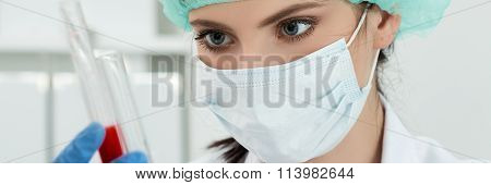 Female Lab Worker Looking At Two Flasks With Dark Red Liquid