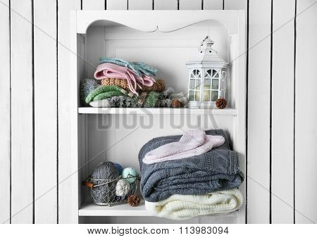 Knitting clothes with accessories on wooden shelf