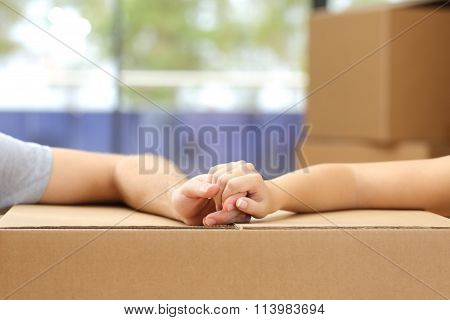 Couple Holding Hands Over A Box Moving Home
