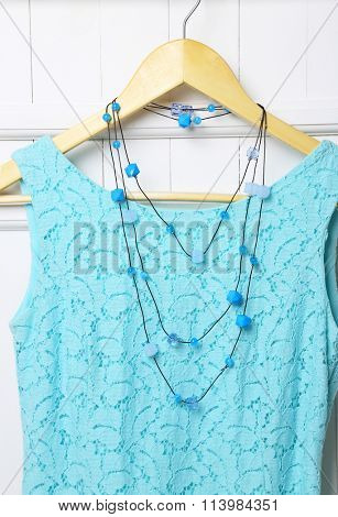 Dress and necklace on hanger on wall background
