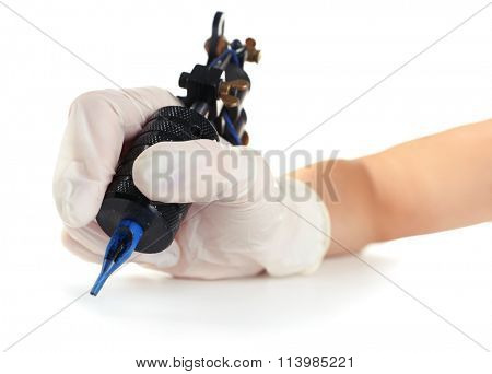 Tattoo machine in hand isolated on white background