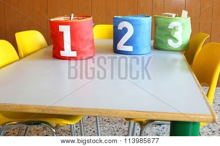 Desk Of A Nursery With Numbered Jars And Small Yellow Chairs
