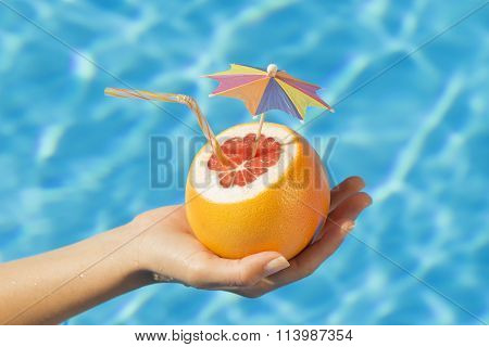 Female hand holding grapefruit above water surface
