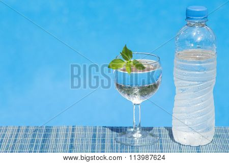 Glass and bottle of water on bamboo straw mat