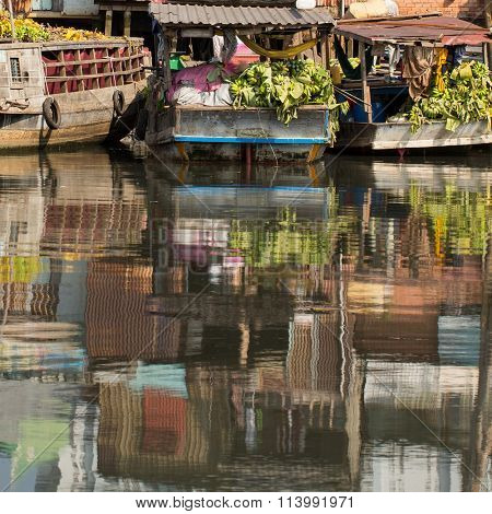 Floating market with reflection in water at Mekong river, Ho Chi Minh city, Vietnam.