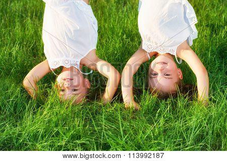 Happy Children Twins Sister Upside Down In Summer