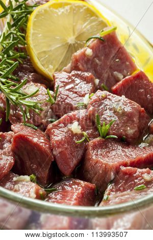 Raw beef cubes marinating in glass bowl with lemon, oil and herbs.
