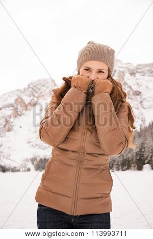 Woman Hiding Behind Collar Outdoors Among Snow-capped Mountains
