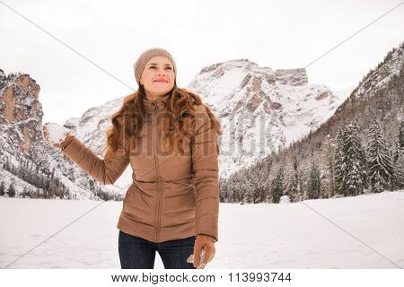 Happy Woman With Snowball Outdoors Among Snow-capped Mountains