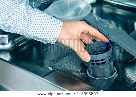 Man's hand taking out a dishwasher filter