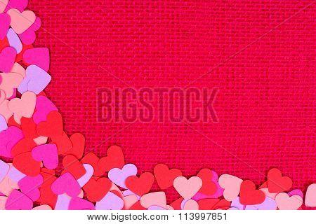 Paper Valentines Day hearts bottom corner border on pink burlap