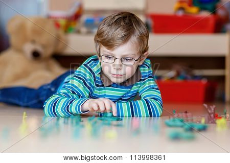 Kid boy playing with toy soldiers indoors at nursery