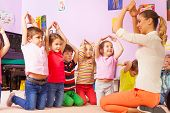 Group of kids repeat gesture after the teacher poster