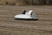 stock photo of hydrofoil  - a small hovercraft is driven across a farm field - JPG