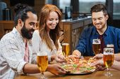 friends eating pizza with beer at restaurant poster